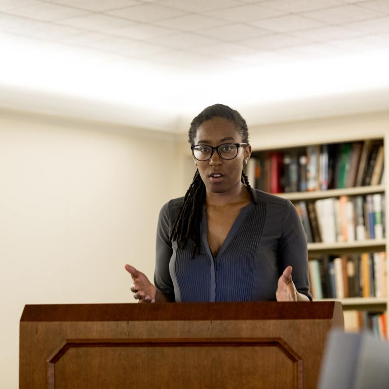 Female graduate student giving a presentation at a podium