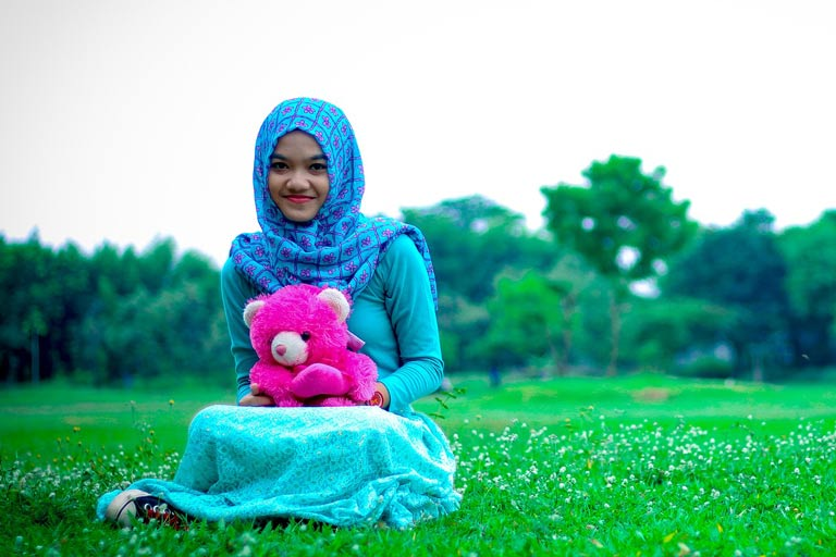 Young girl wearing a headscarf holding a stuffed toy bear