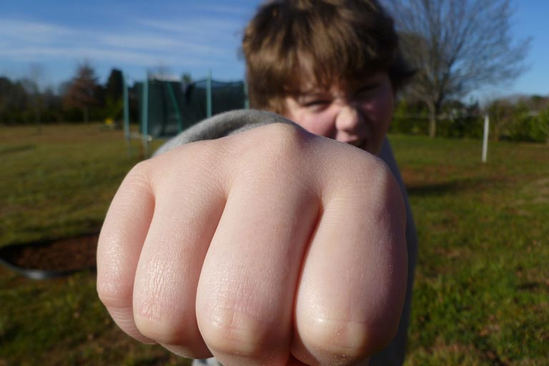 Young boy giving a fist bump to the camera