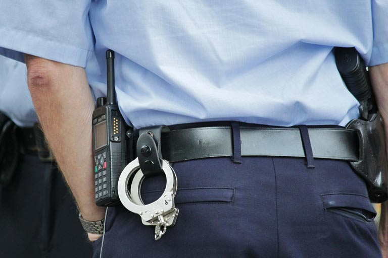 Close up of a policeman's belt with a radio and handcuffs strapped to the back